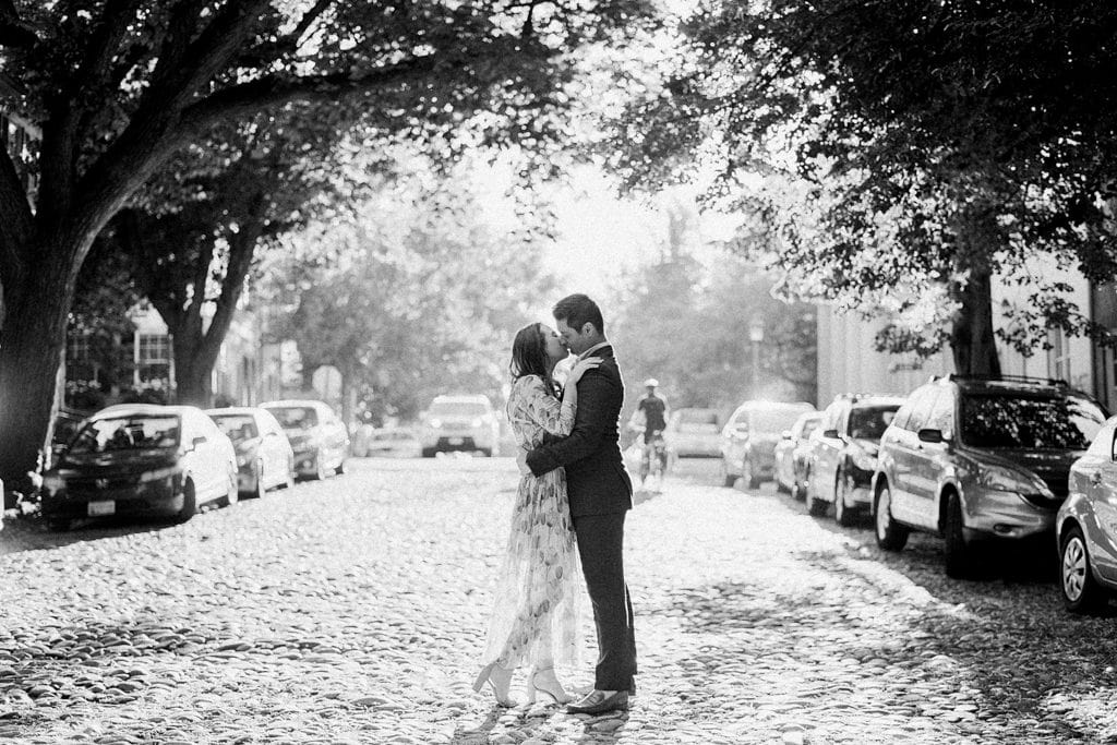 Couple kissing on a cobble stone street in Old Town Alexandria Virginia