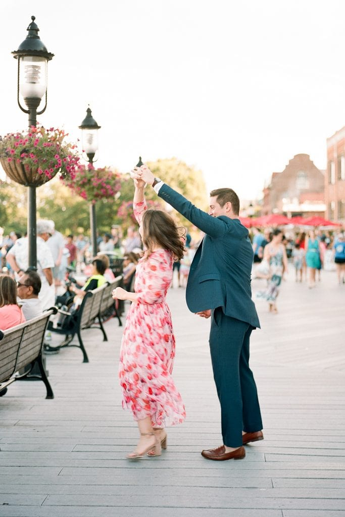 Couple walking and dancing and holding hands on the dock in Old Town Alexandria