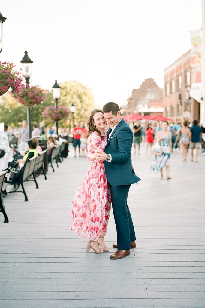 Couple dancing and holding hands on the dock in Old Town Alexandria
