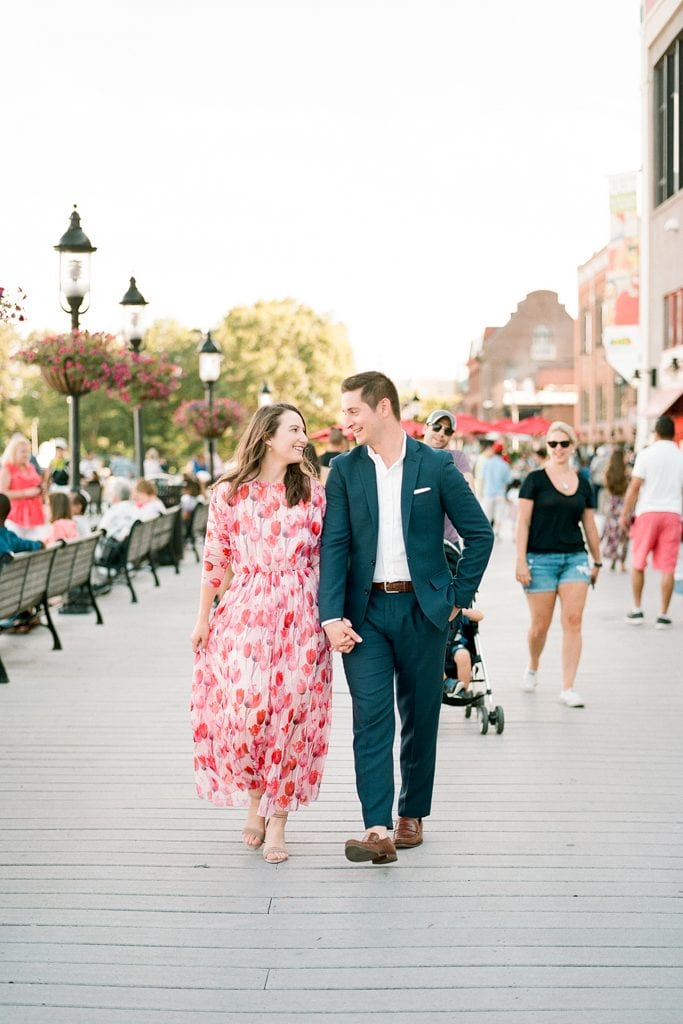 Couple walking and holding hands on the dock in Old Town Alexandria