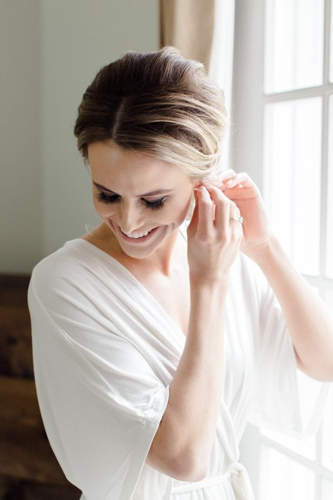 The Pennsylvanian Wedding Bride putting earnings in hair and makeup beauty justified by Justine Lynn- White and Gold Wedding at The Pennsylvanian