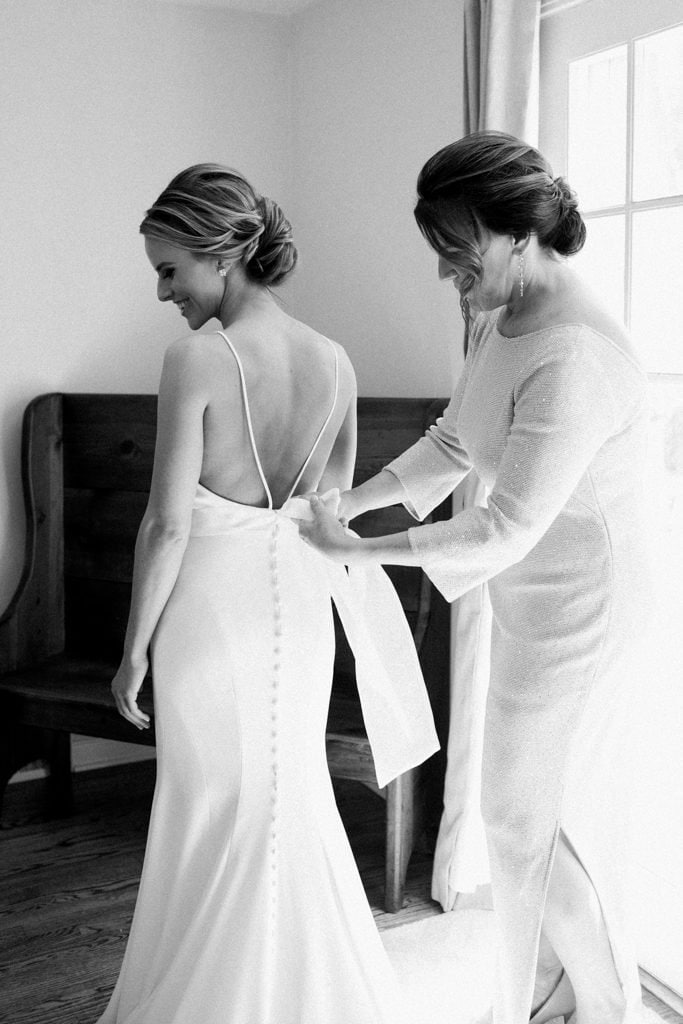 The Pennsylvanian bride getting dressed in Mikaella by Paloma Blanca bridal dress