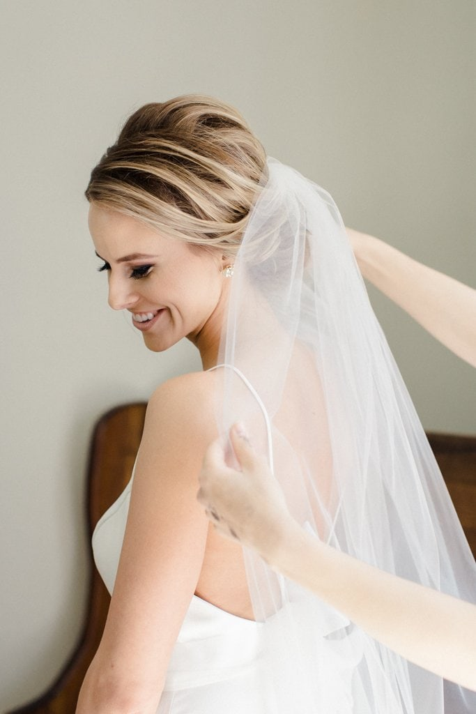 The Pennsylvanian Wedding Bride getting veil put on hair and makeup beauty justified by Justine Lynn - White and Gold Wedding at The Pennsylvanian