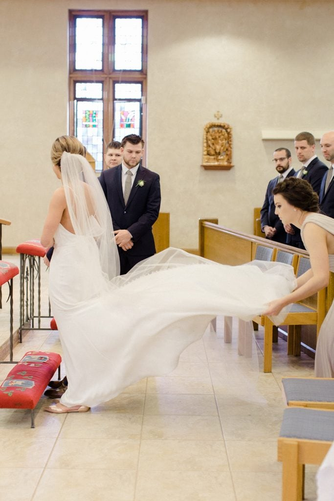 The Pennsylvanian Wedding fluffing bride's paloma blanca dress at St. Bede's Church