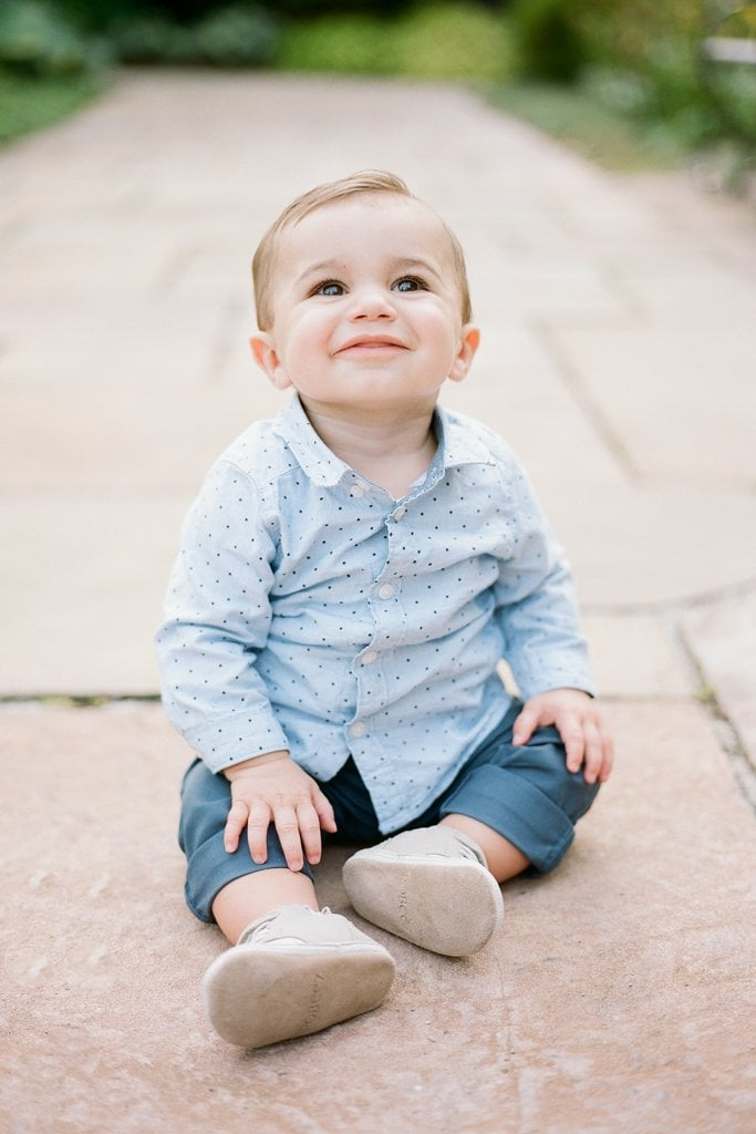 Baby smiling during photos while sitting on the ground
