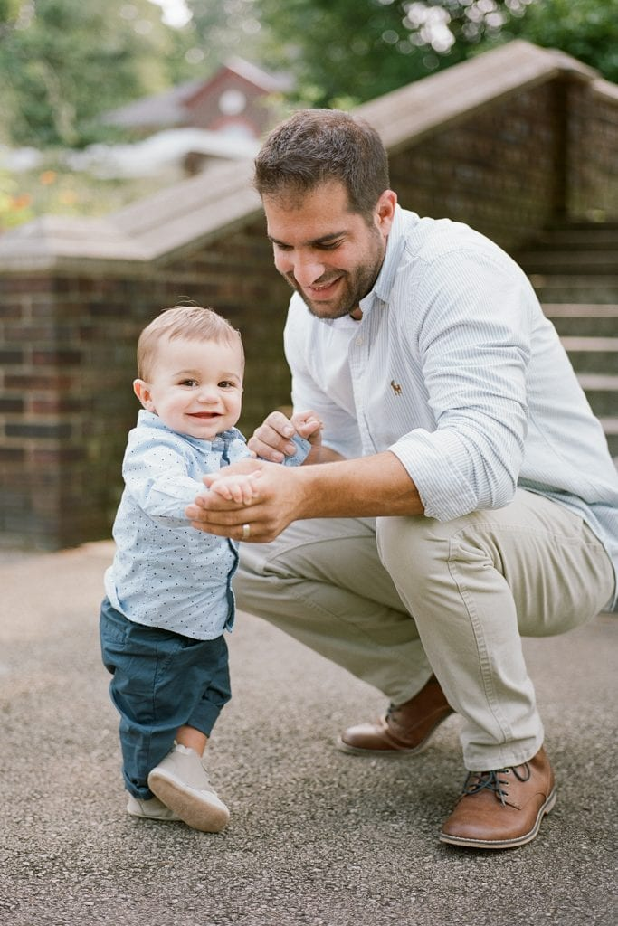 Dad holding his son's hand while crouching near him during Family Session at The Walled Garden