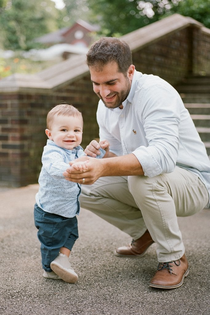 Dad holding his son's hand while crouching near him- Family Session on Film at the Walled Garden, Mellon Park