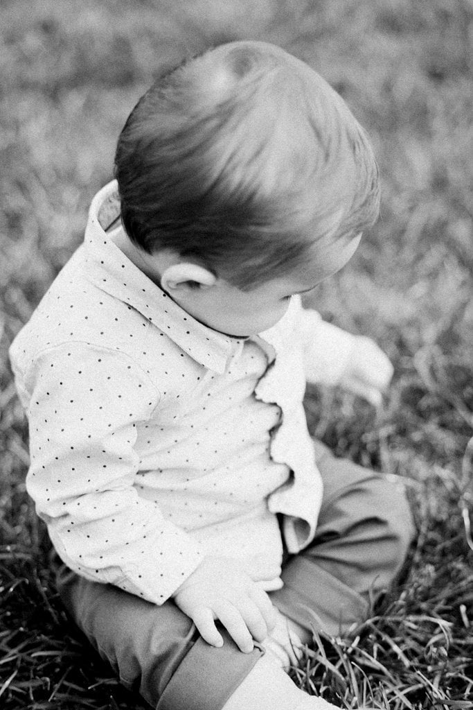Black and white photo of baby playing in the grass - Family Session on Film at the Walled Garden, Mellon Park