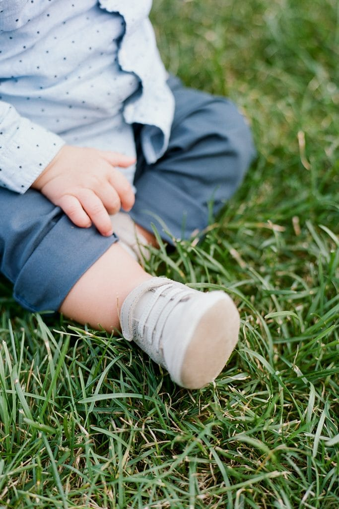 Baby shoes and hands on the grass