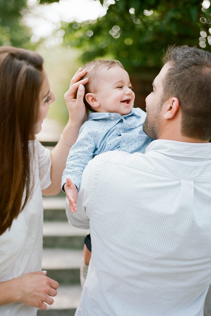 Mom and Dad kissing and tickling baby boy during Family Session at The Walled Garden