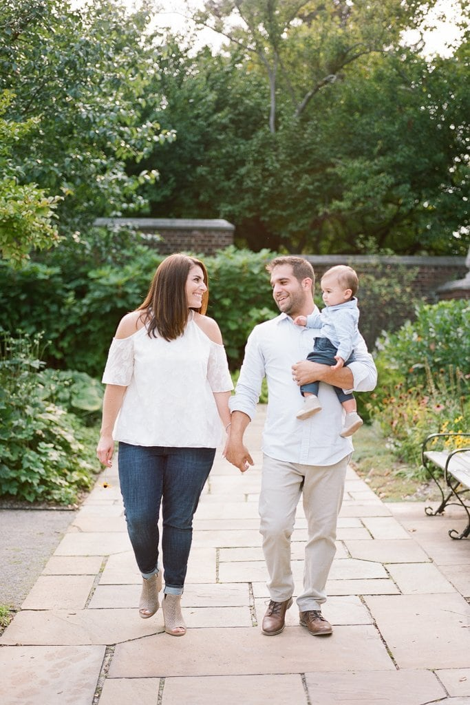 Mom and dad holding hands while walking and holding the baby - Family Session on Film at the Walled Garden, Mellon Park