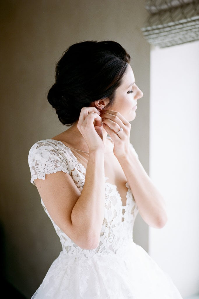 Bride putting on her earrings while getting ready for her wedding day