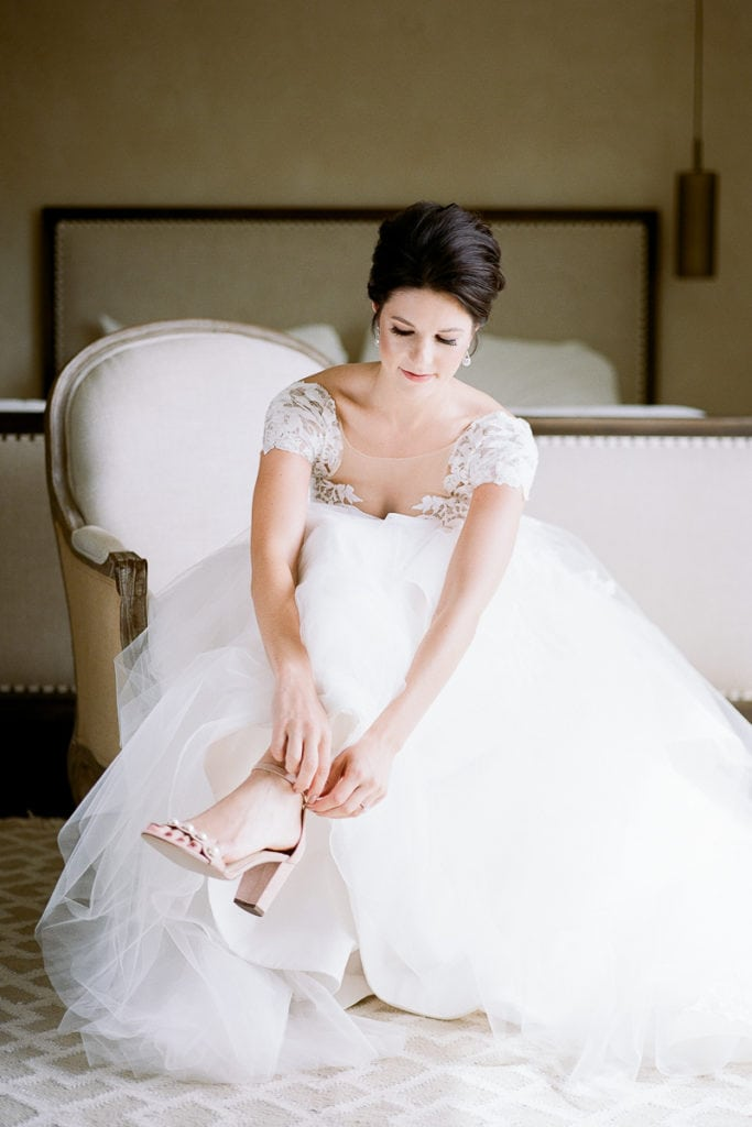 Beautiful bride putting on her wedding shoes