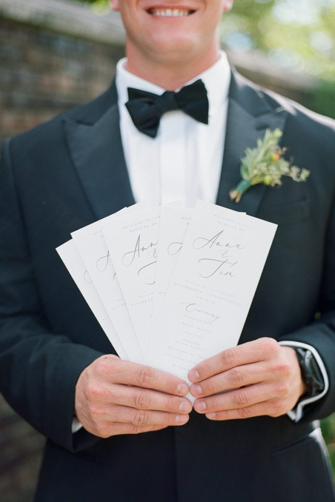 Ceremony programs held by a groomsmen
