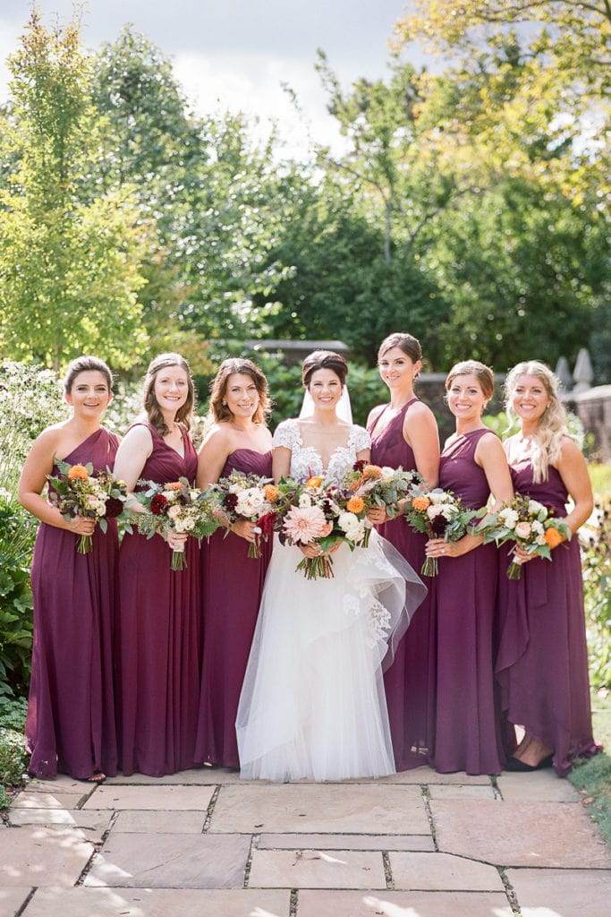 Bridesmaids dressed in plum purple dresses for fall wedding