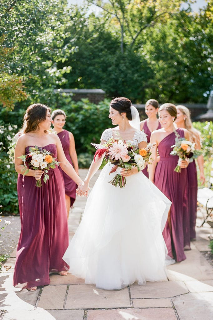 Bride walking and smiling with her bridesmaids