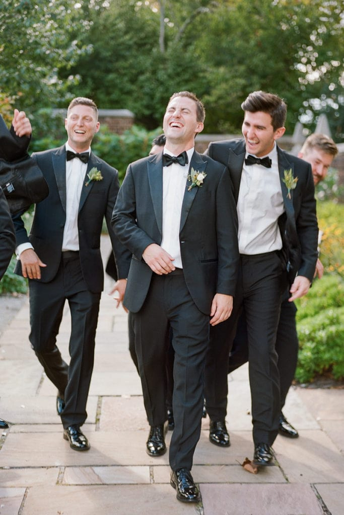 Groom laughing and joking with his groomens
