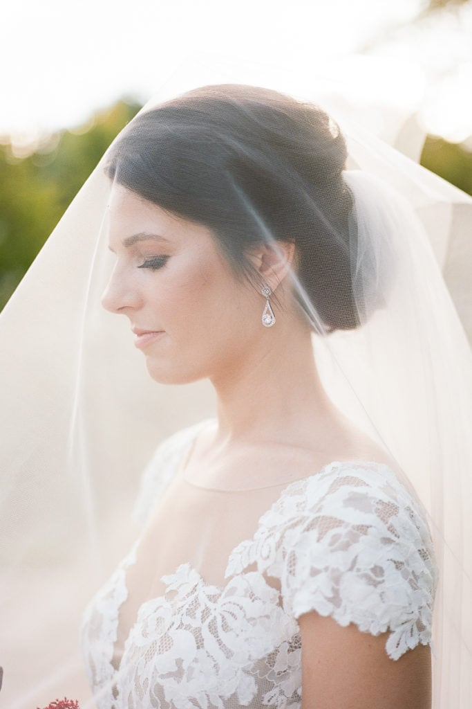Bride under her veil with the sun shining through