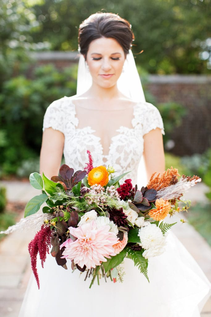 Bride holding her fall colored bouquet from the Farmer's Daughter