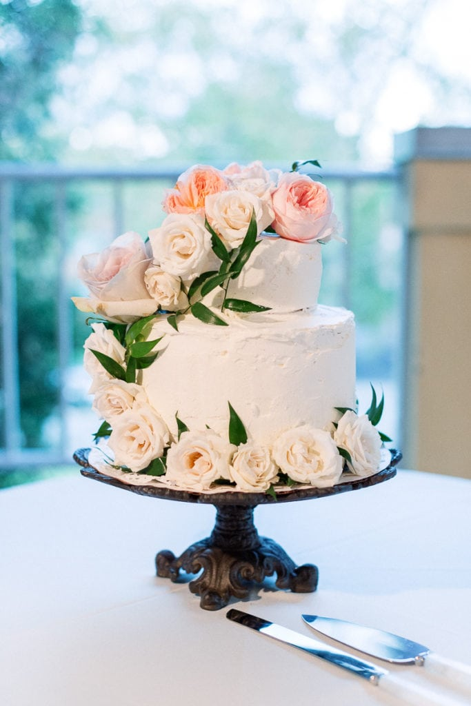 Wedding cake decorated with light pink flowerrs