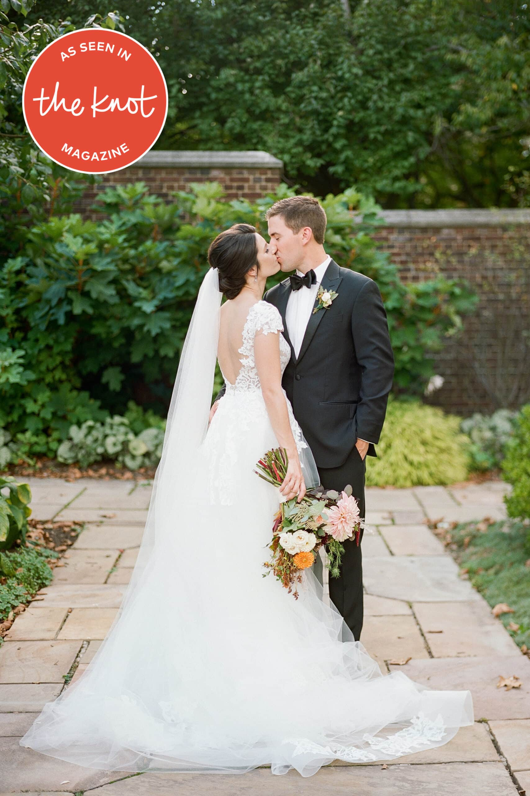 Bride and groom standing in the walled garden kissing