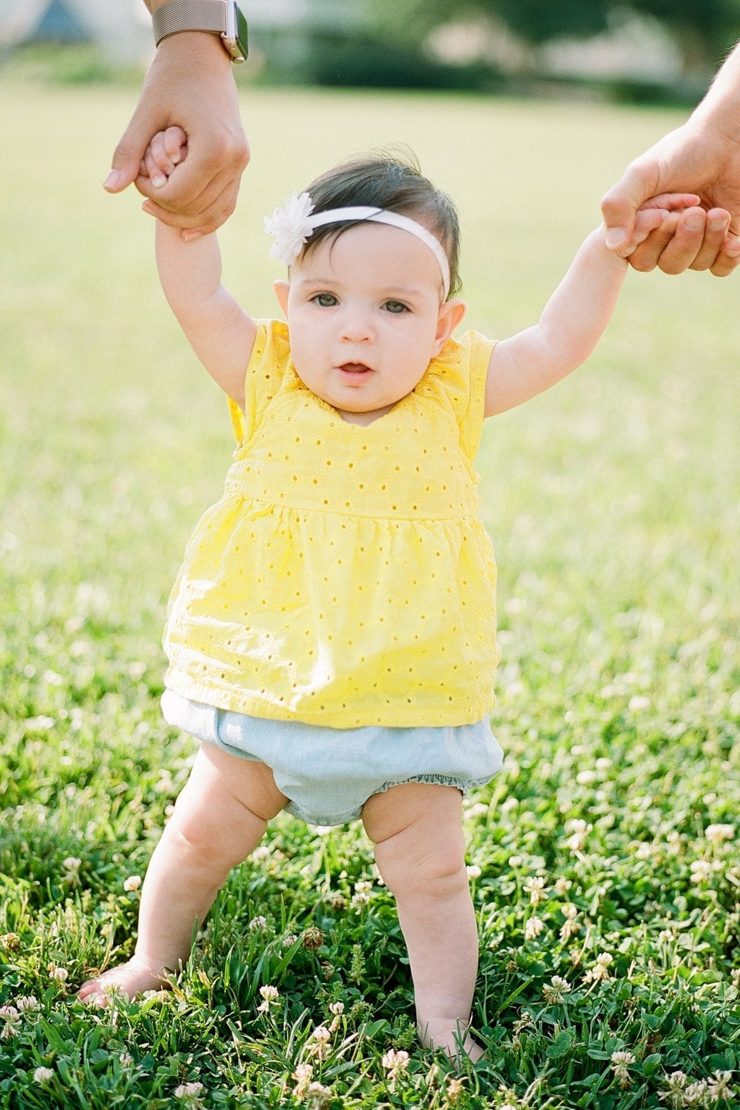 Little girl holding her parents hands while standing in grass wearing a yellow top