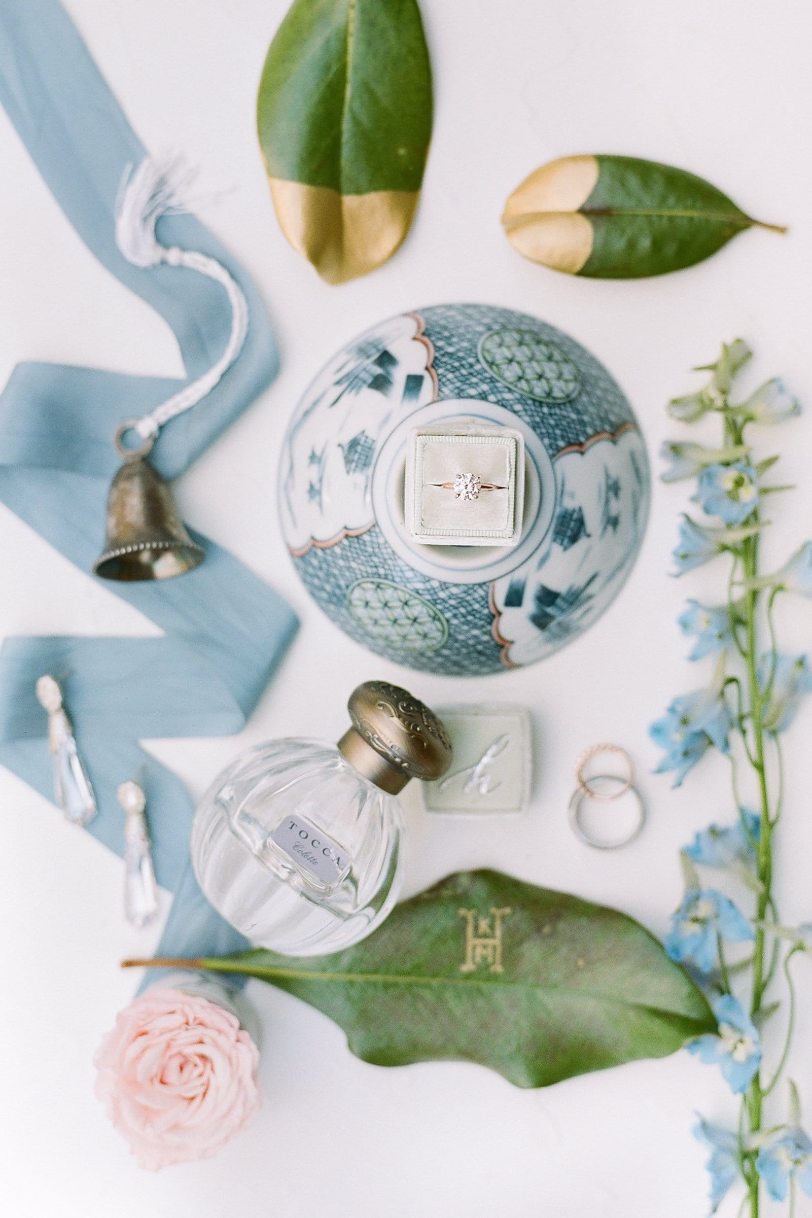 mrs. box and tocca perfume bridal details with calligraphy name tags and bell
