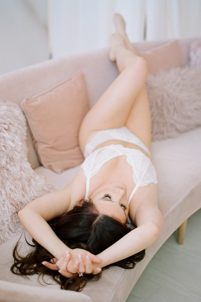 elegant bridal boudoir woman laying on a pinch couch in white lingerie