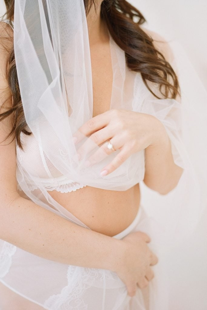 woman wrapped in bridal veil wearing white lingerie
