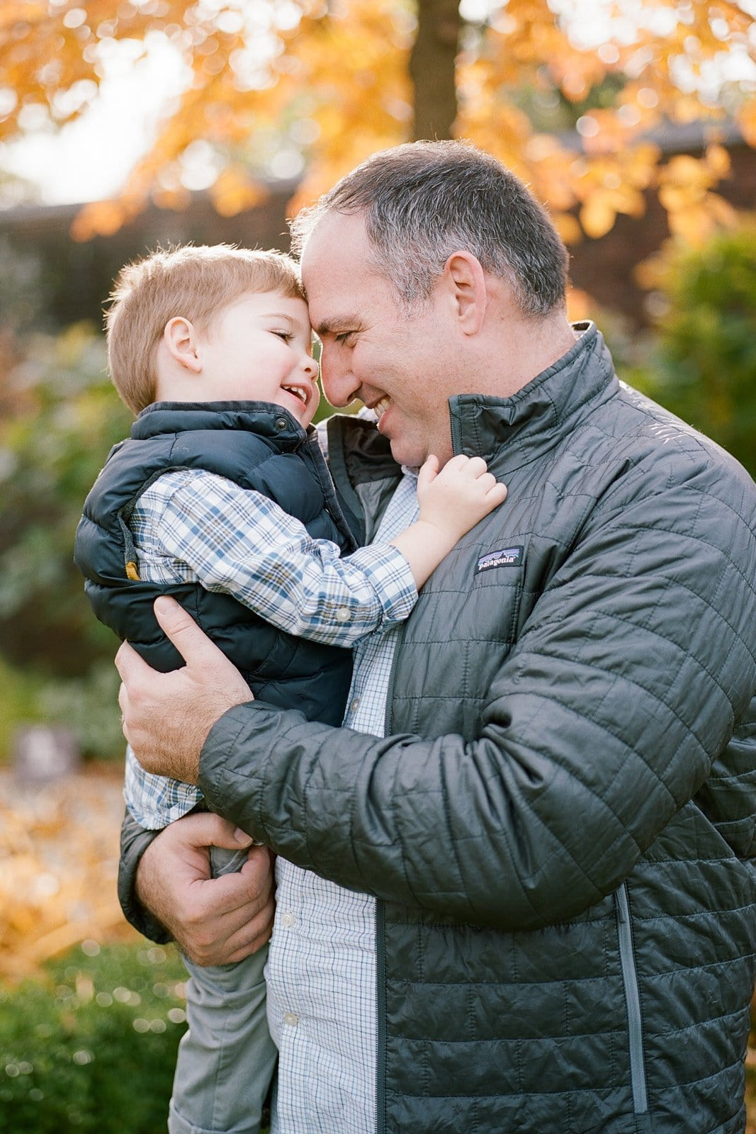 Dad embracing his son and touching foreheads during photos
