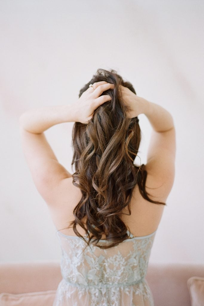 photo of the back of a woman and her hands through her hair