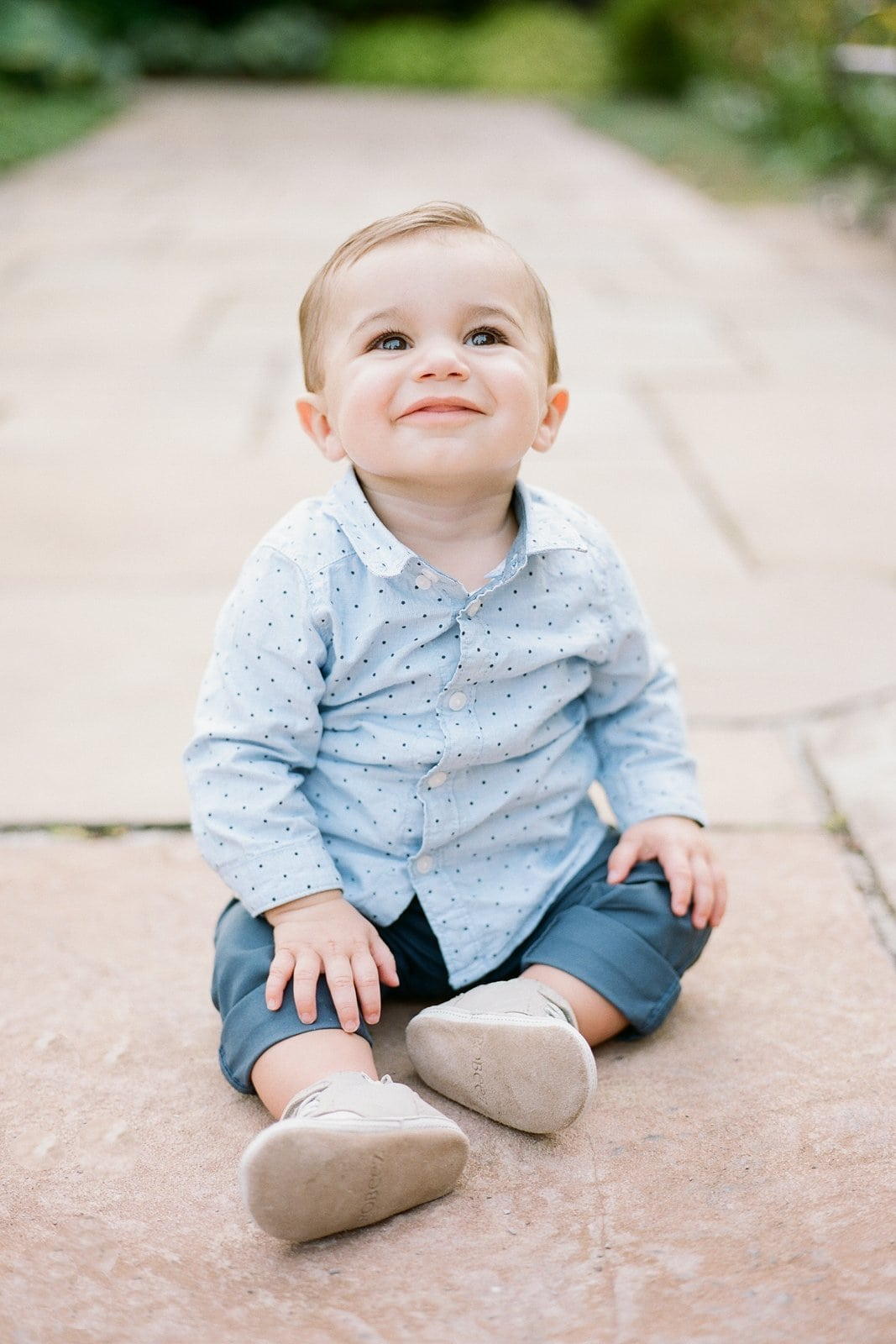 toddler sitting on the ground at the park in blue shirt and pants