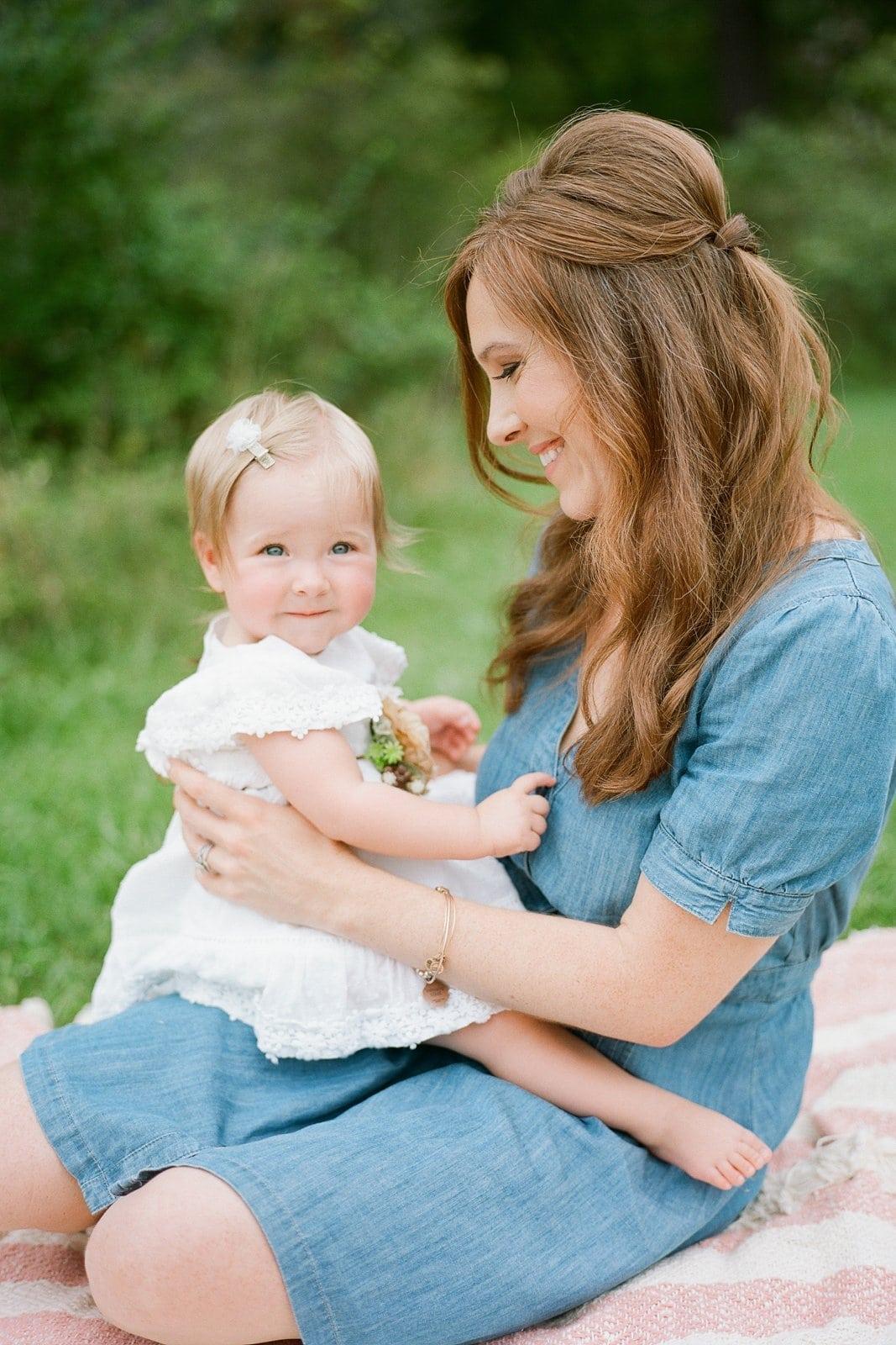 Mom holding her little girl in her lap