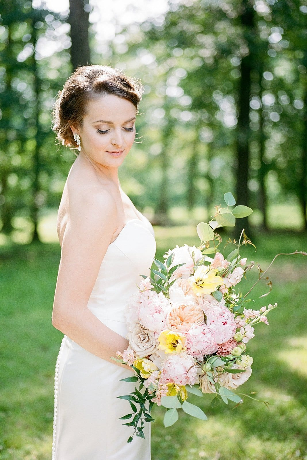 bride holding pink and orange bouquet in sunlight