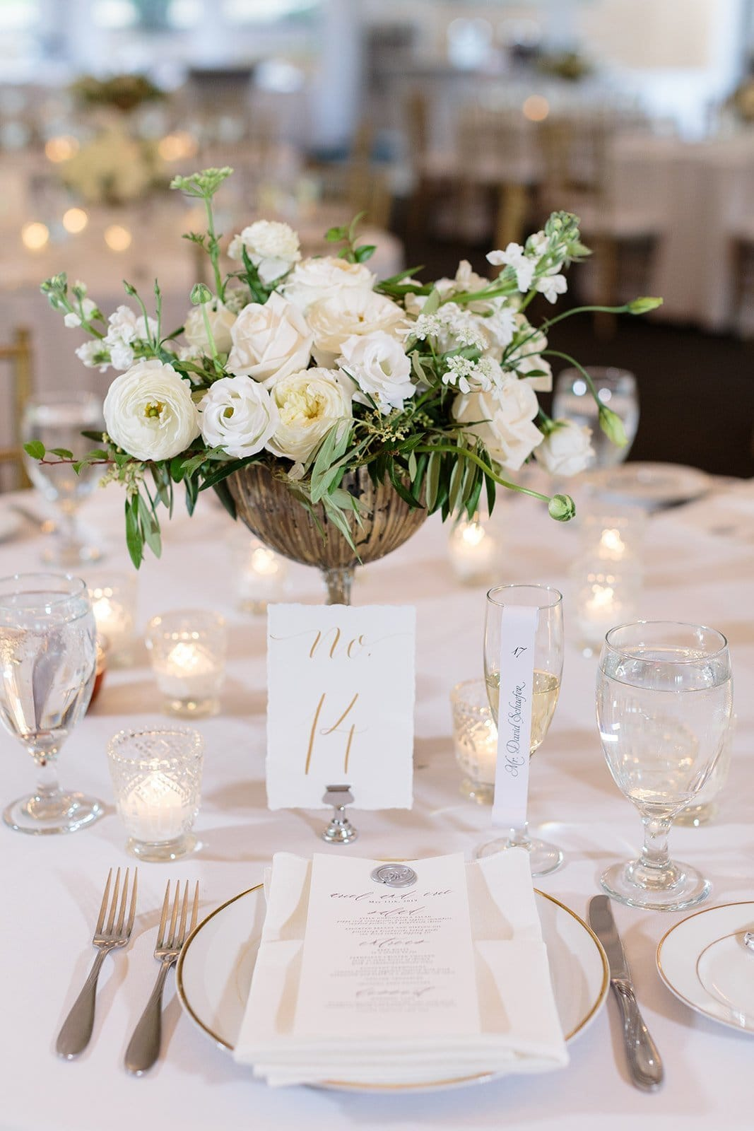 escort card table with champagne flutes and rolled paper