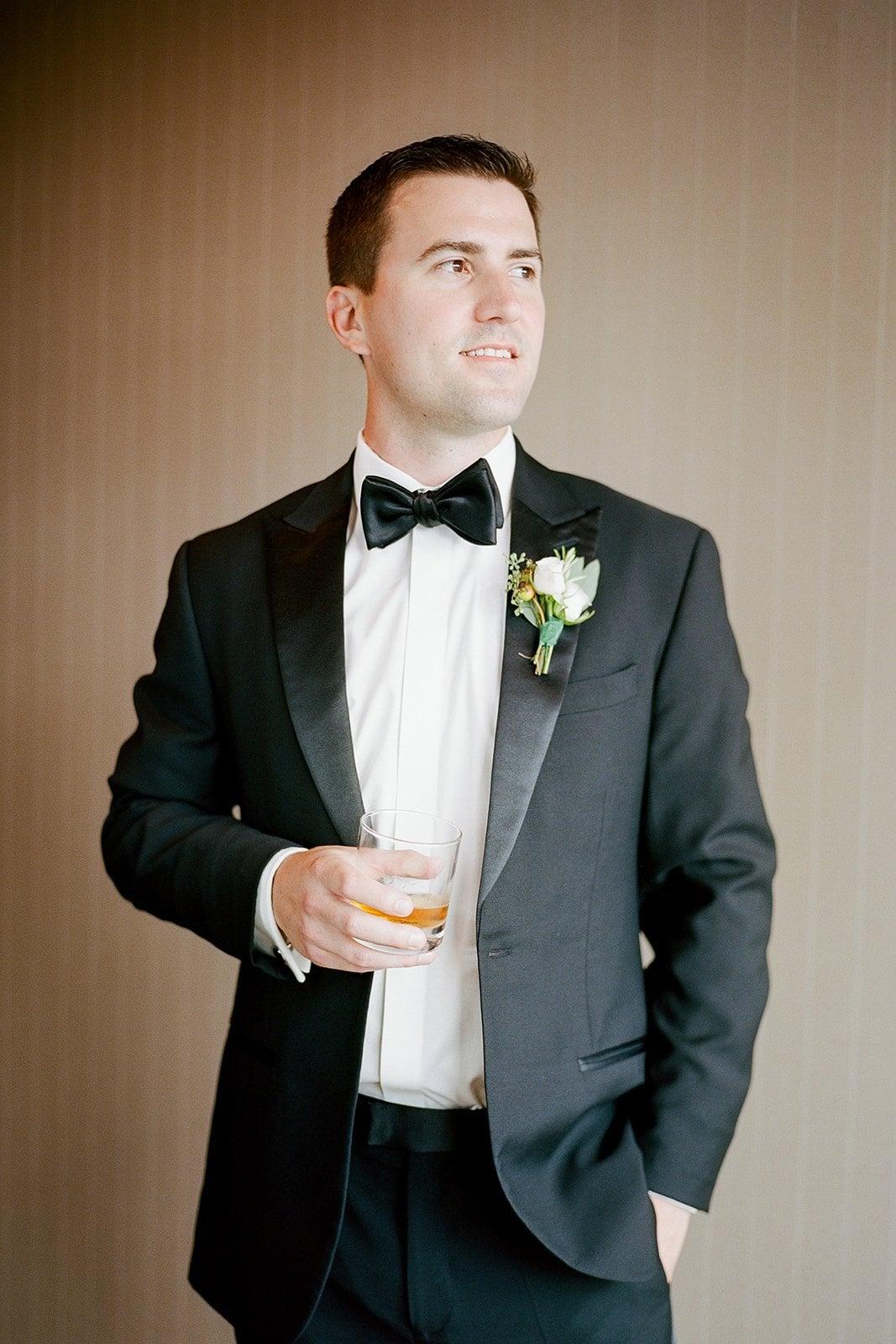 groom holding a scotch in a tuxedo
