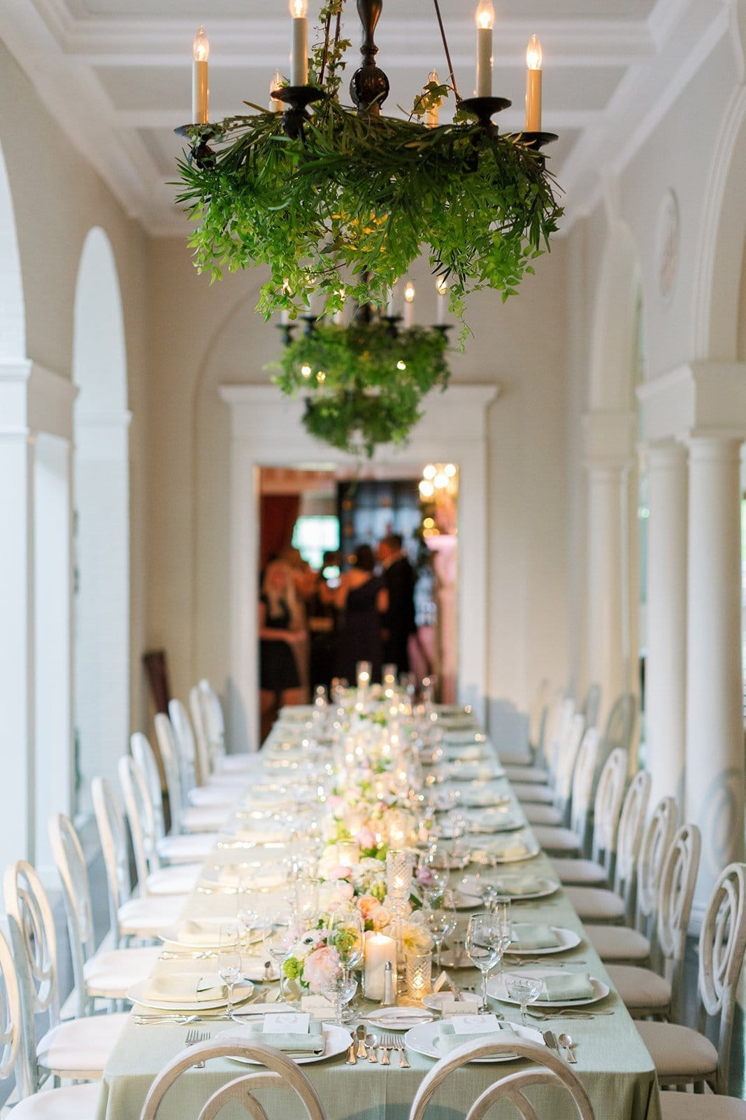 long head table with chandeliers covered in greenery