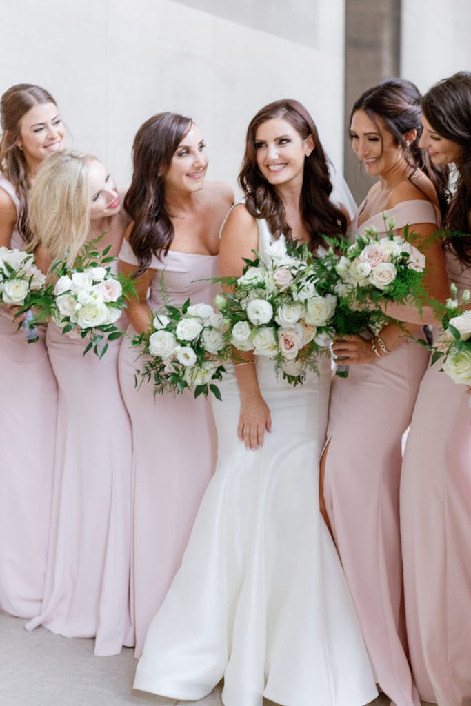 Bridesmaids in light pink dresses at the mellon institute columns