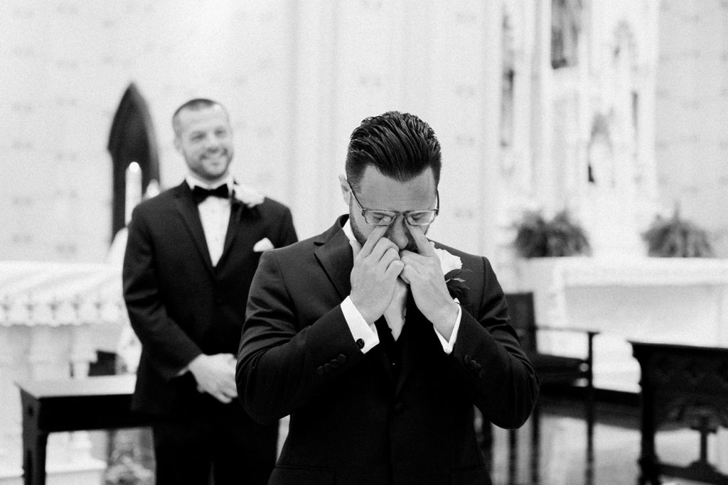 Groom seeing his bride walk down the aisle for the first time