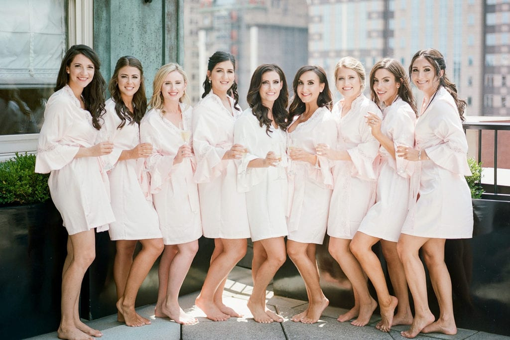Bride with her bridesmaids in robes on rooftop of Renaissance Hotel