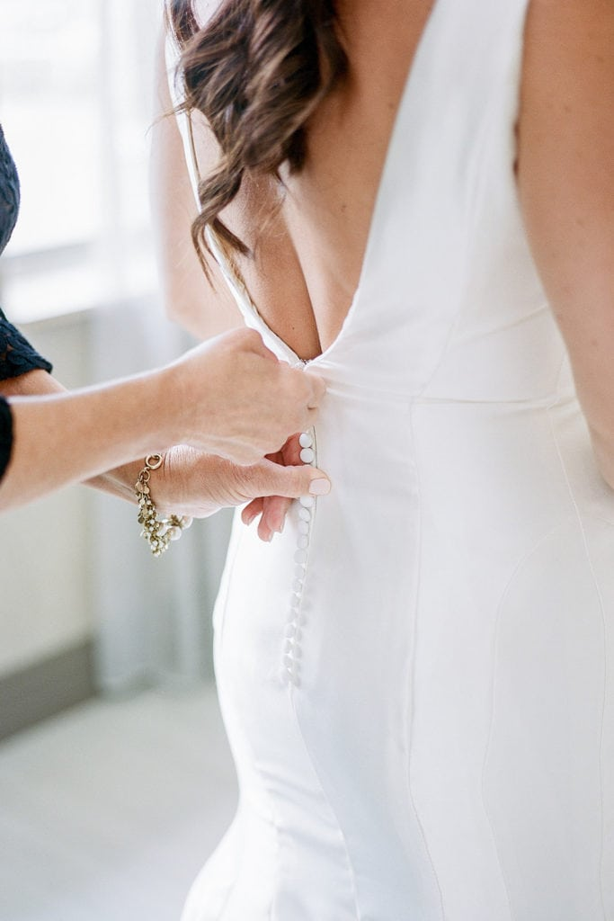 Bride getting zipped into her Sareh Nouri dress from Bridal Beginnings