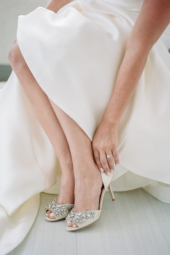 Bride putting on her badgley mischka shoes