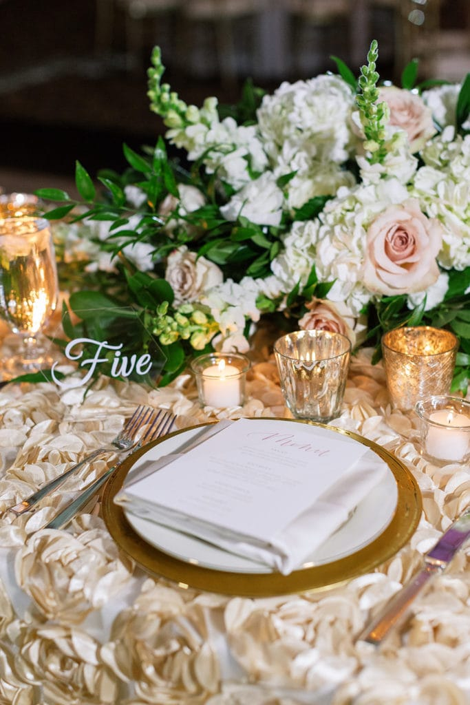 Place setting with pink and gold accents and mosaic linens