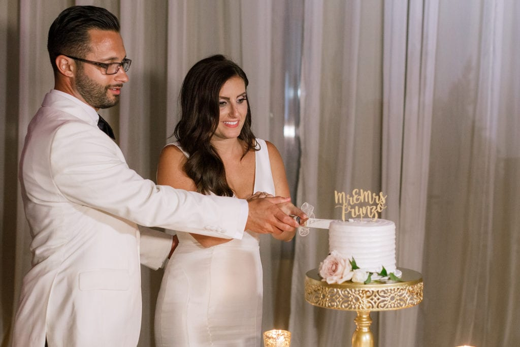 bride and groom cut their Oakmont Bakery wedding cake