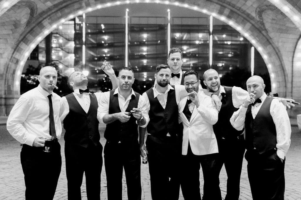 Groomsmen enjoying cigars outside in the rotunda of the Pennsylvanian