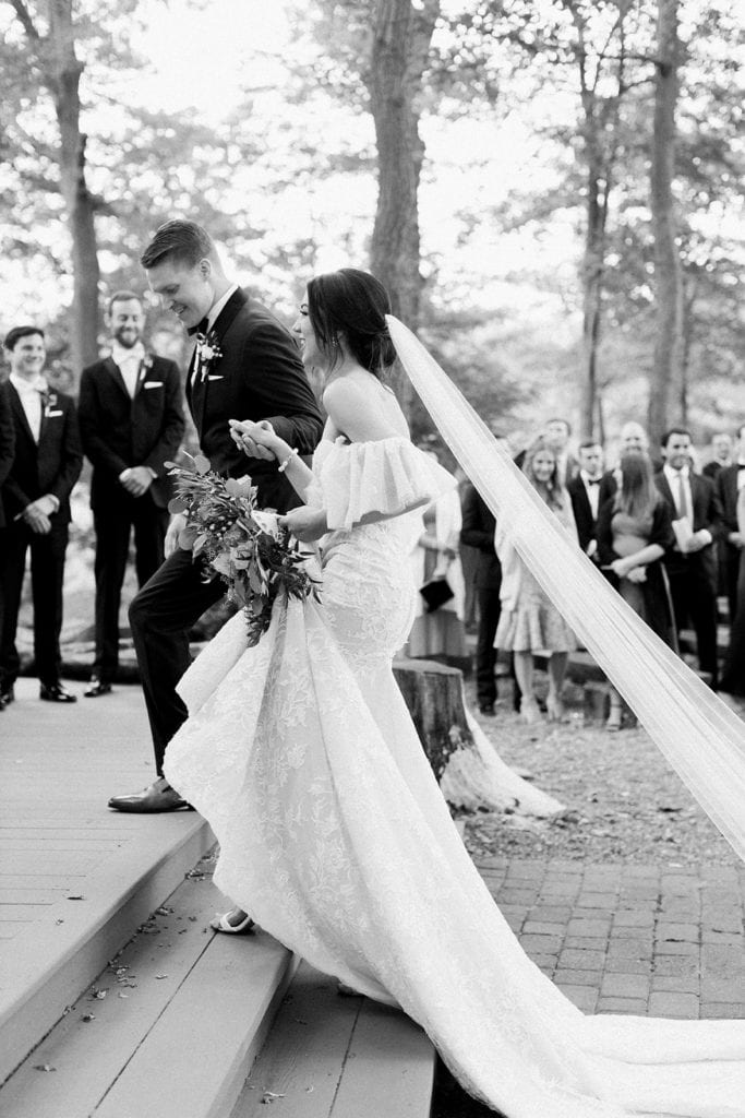 Groom escorting his bride up to the altar for their wedding ceremony