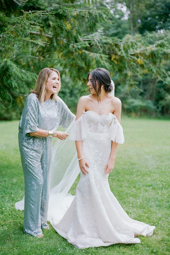 Mother of the bride helping her daughter into her Berta Bridal Wedding Gown