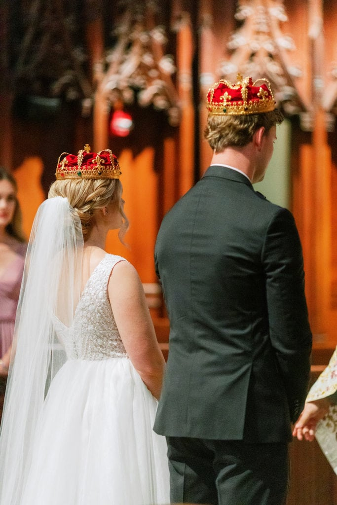 Bride and groom wearing Roman Catholic Crowns during ceremony at Heinz Chapel