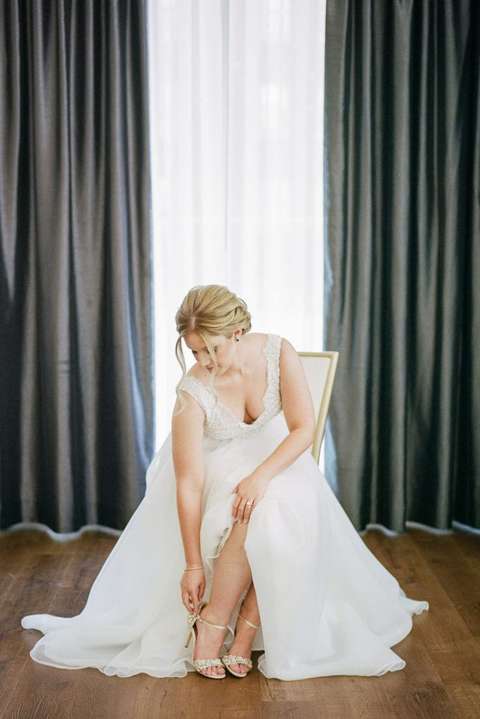 Bride putting on her Badgley Mischka wedding shoes