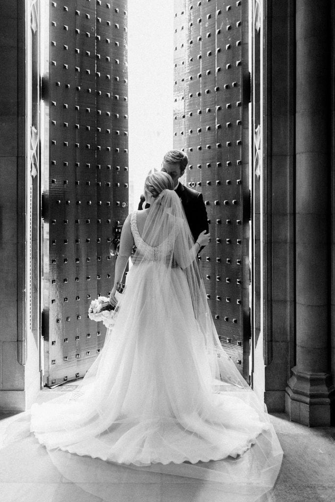 Black and white photo of bride and groom portraits inside Heinz Chapel